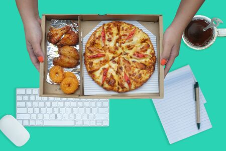 Hand holding pizza, fish rings and grilled chicken wings in paper box, Working space on table on background.