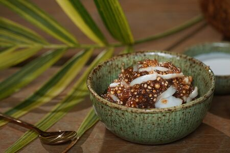 Tapioca pearls form sago tree. Still life photography of Thai dessert Sago palms with coconuts or sago pearls in coconut milk on the table. Popular dessert in Thailand served with fresh coconut milk.