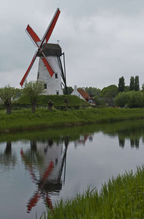 Windmill along canal with reflection in Damme Flanders Stock Photo