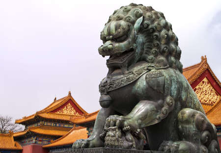 Beijing Forbidden City: lion statue against the roofs.