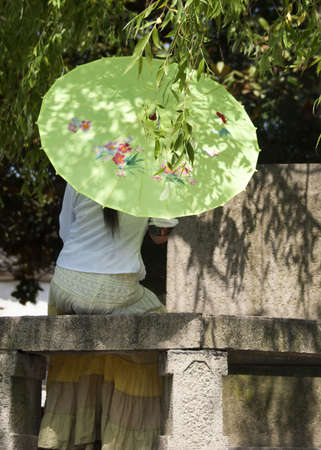 Tongli: lonely lady under umbrella caught in romantic thought.