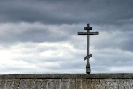 Orthodox cross on top of roof against rainy skies.