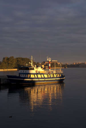 Early morning shoots golden rays onto small boat in the port of Saint Petersburg Russia.