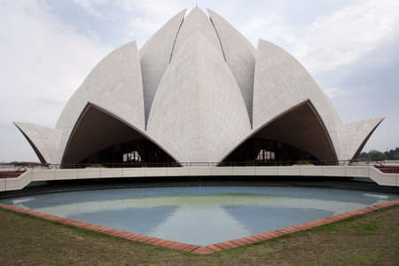 Lotus shaped top of the Bahai temple reflected in one pool.