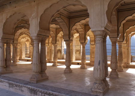 Gallery of rimmed pillars in light sunshine at Jaipurs Amber Fort.