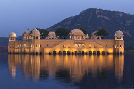rajasthan: Lighted Summer Palace in Indias Jaipur on the lake under evening skies.