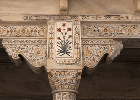 Beautiful marble lay-in work of flowers on pillar top and support at Agra Fort Palace in India. Yellows, reds and dark greens against beige marble surfaces. Editorial