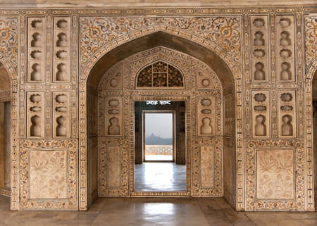 Decorated marble wall frames gate and door at Agra Fort Palace in India. Alcoves and yellow red green in-lay marble work of royal chambers, Taj Mahal in the far distance.
