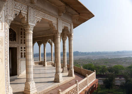 Columned viewing point outside royal chambers at Agra Fort Palace in India. Wide view over Yumana river and surrounding land out of decorated marble patio.