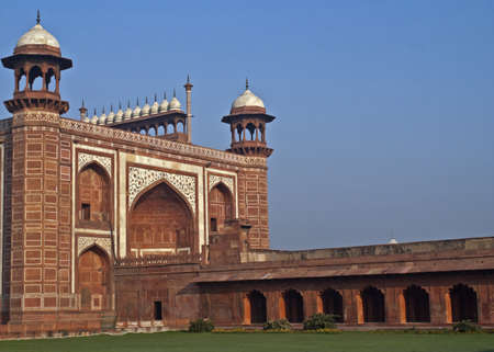 Green lawn, blue skies, red walls, and white marble decorations topped by a line of chhatris. photo