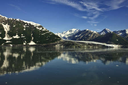 Flanked by mountains the grey white glacier under blue skies is mirrored in sea water. photo