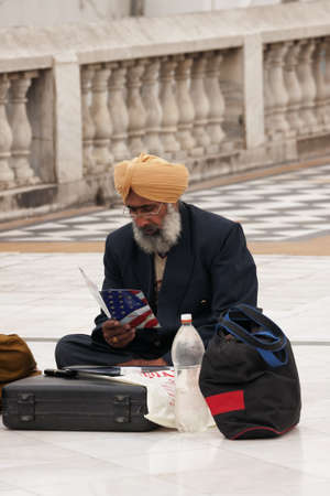 emigrant: New Delhi - March 2011 - Sikh emigrant, sitting on the pavement,  studies how to get legally into the USA.