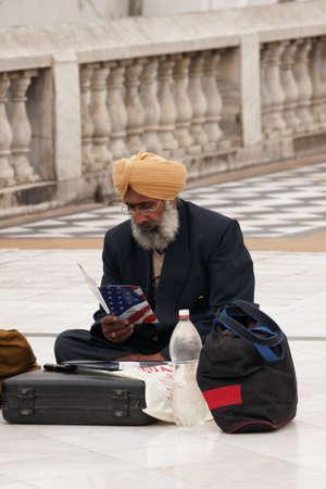 New Delhi - maart 2011 - Sikh emigrant, zittend op de stoep, onderzoekt hoe om legaal te krijgen in de VS.