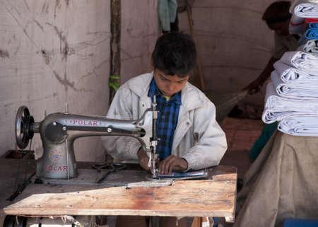 Nagaur in Rajasthan India - februari 2011 - Kinderarbeid: jongen naaien in stand op de markt.