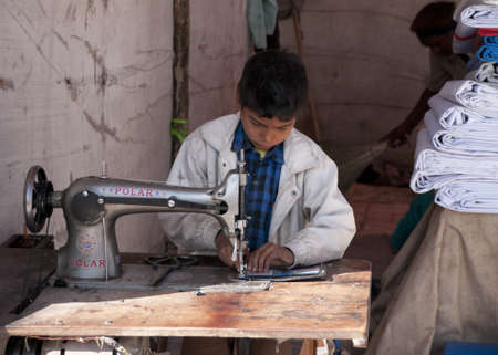 Nagaur in Rajasthan India - February 2011 - Child labor: boy sewing in booth on the market.