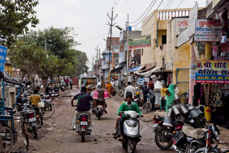 Agra in India - February 2011 - Heavy traffic in side street wth a few small shops and where milk is delivered by motorcycle.