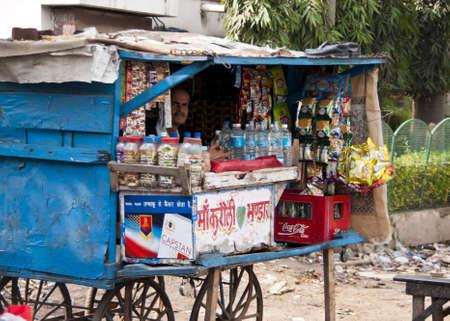 Indiase stad Agra - februari 2011 - Street vendor verkoopt levensmiddelenwinkel producten in een typische kleine hokje op wielen.