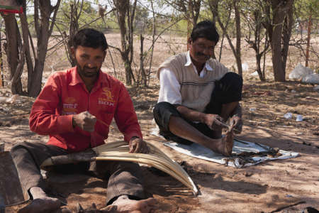 Nagaur in Rajasthan India - February 2011 - Two hand laborers making wooden hay forks in the desert while supporting the Chicago Sox.