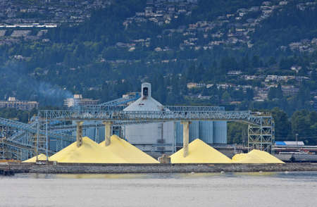 Yellow piles against blue silos in front of the mountains. Stock Photo
