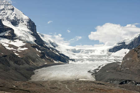 The white glacier capped by blue skies descends in brown dry valley. Reklamní fotografie