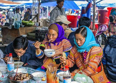 sunday market: Vietnam Bac Ha - marzo de 2012: personas de etnia hmong alimenticios en el mercado dominical. Editorial