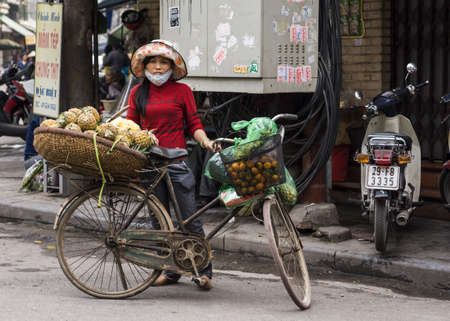merchant: Vietnam Hanoi - March 2012: Female street vendor selling pineapples out of a basket on her bicycle. Editorial