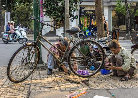 harmed: Vietnam Hanoi - March 2012: Bike repair business on a corner of the street.