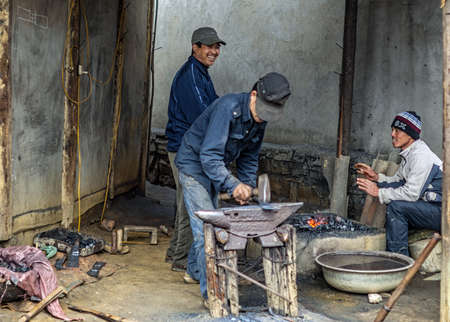 Machete factory black smith at Sunday Market. Men beating the metal on anvil while fire burns. Editorial