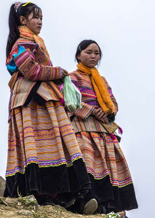 Two young Hmong sisters show and wait at Sunday market. Colorful traditional dress against white sky.