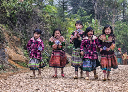Group of young girls on farm road in mountains. Five young beauties in colorful traditional dress with wild flowers and big smiles. Editorial