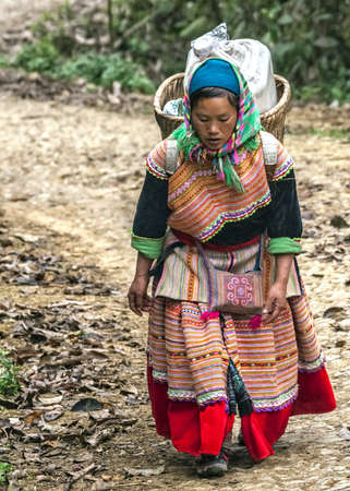 Hmong woman with loaded basket on her back comes around the bend in the road. Colorful appearance.