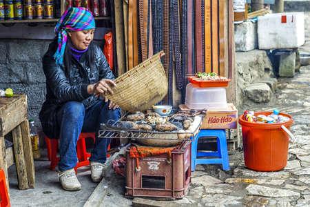 Cat Cat. Vietnam - 3 maart 2012: Hmong vrouw verspreidt rook van primitieve gebraden put.