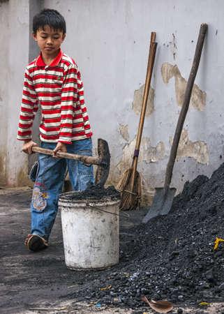 Duong Lam, Vietnam - 8 maart 2012: Jongen scoops steenkool in emmer te nemen in huis. Kid met kleurrijke overhemd maakt gebruik van schop om zwarte steenkool in de witte emmer.