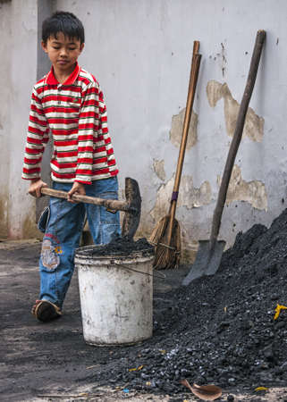 Duong Lam, Vietnam - March 8, 2012: Boy scoops coal in bucket to take inside home. Kid with colorful shirt uses shovel to put black coal in white bucket. Publikacyjne