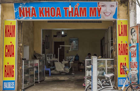 Duong Lam, Vietnam - March 8, 2012:Dental office in rural village. Front of office framed in advertisement posters looks into dental workplace. Editorial
