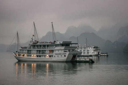 ハロン湾、ベトナム - 2012 年 3 月 13 日: クルーズのジャンク船は、石灰岩の山の前に早朝の霧の下に座って。おとぎ話に出て神秘的なロマンチックな 報道画像