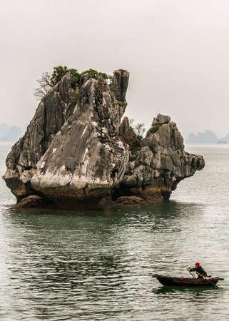 ベトナム ハロン湾 - 2012 年 3 月: 壮大な石灰岩の岩の前で唯一の手漕ぎボートの旅。エアフロー カバーの他の山の霧の朝の空。