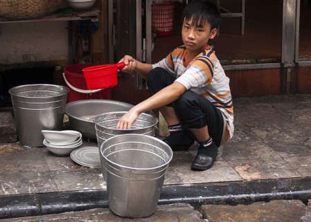 Vietnam Hanoi - March 2012: Doing the dishes on the sidewalk in front of street restaurant. Sad looking young boy rinsing plates in metal buckets.