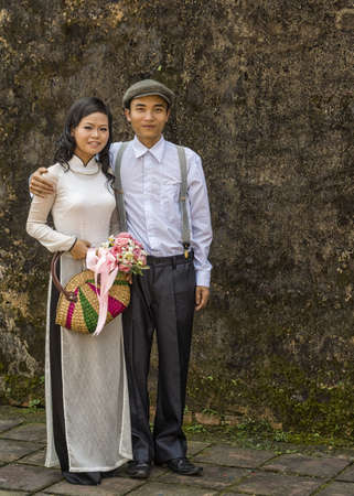 cherishing: Young couple against the rampart, she in Ao Dai, he with suspenders and classic workers cap.