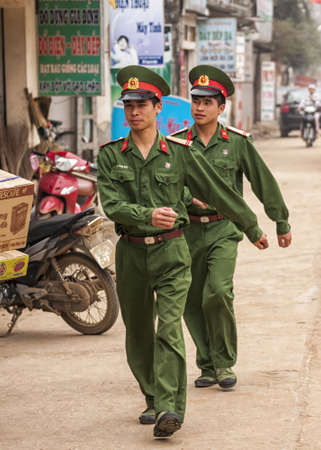 rural town: Vietnam Red River Delta - March 2012: Two marching soldiers in the street of rural town.