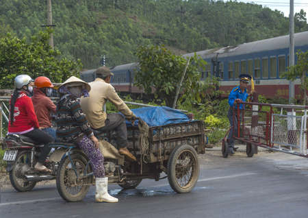 Central Vietnam - March 2012: The guard closes the railway fence to let the train pass, while motorbike riders wait.