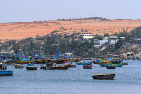 South Vietnam Mui Ne village  The dunes tower over the sea with its many fishing vessels  Stock Photo