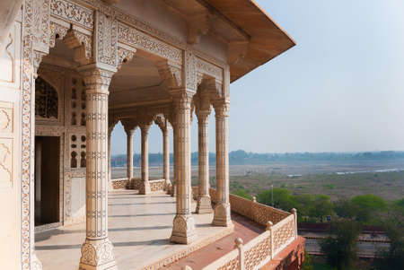 Columned viewing point outside royal chambers at Agra Fort Palace in India  Wide view over Yamuna river and surrounding land out of decorated marble patio