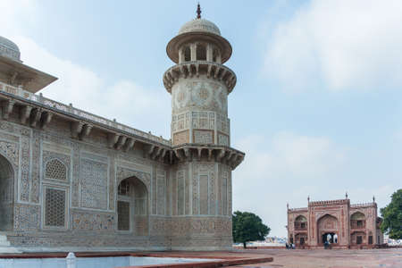 west gate: Minaret of Agra s Baby Taj mausoleum with West gate in the background, India  Combination shot of white marble edifice and red white gate building both against blue cloudy skies  Stock Photo