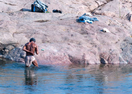 ORCHHA, INDIA - CIRCA FEBRUARY 2011  Man standing in the cold water of Betwa River washing himself with soap  Editorial