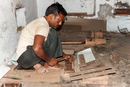 benares: VARANASI, INDIA - CIRCA FEBRUARY 2011  Man punches manually holes in carton guide for Jacquart weaving machine