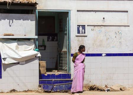 BENGALURU, INDIA - CIRCA oktober 2013 Openbaar toilet Vrouw verantwoordelijk bewakers de ingang van het lazarus wc