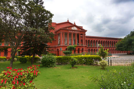 View from the street on red brick building known as Attara Kacheri, the seat of the High Court, and gardens in Bangalore  Editorial