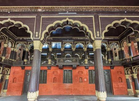 Hall de recepción y en el Real Box en Tipu Sultan Palace en Bengaluru pilares de teca, paredes de color crema y arcos pintados de rojo de pavo real Foto de archivo - 25091912