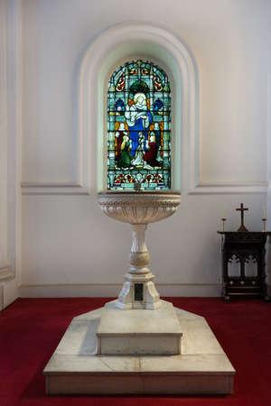 Bautismal imagen de la fuente debajo de la ventana de cristal manchada en la catedral de San Marcos s en Bengaluru